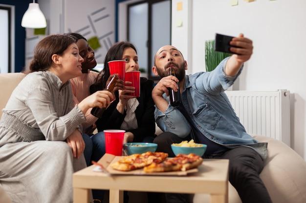 Разнообразная группа сотрудников, делающих селфи на смартфоне