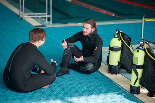 Divers in scuba gear leisures after dive lesson