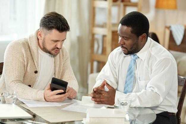Разнообразные взрослые мужчины сидят за столом с бумагами и счетной машиной, обсуждая ипотеку