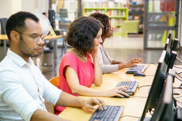 Diverse adult students working in computer class