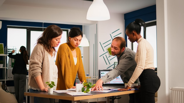 재무 문서를 살펴보고 책상 위에 서 있는 비즈니스 사무실에서 의사 소통하는 다양한 비즈니스 사람들. 현대 직장에서 회사 정보를 분석하는 다민족 팀