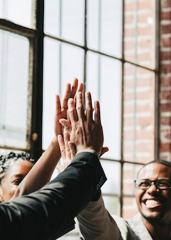 Diverse business people giving a high five in the middle