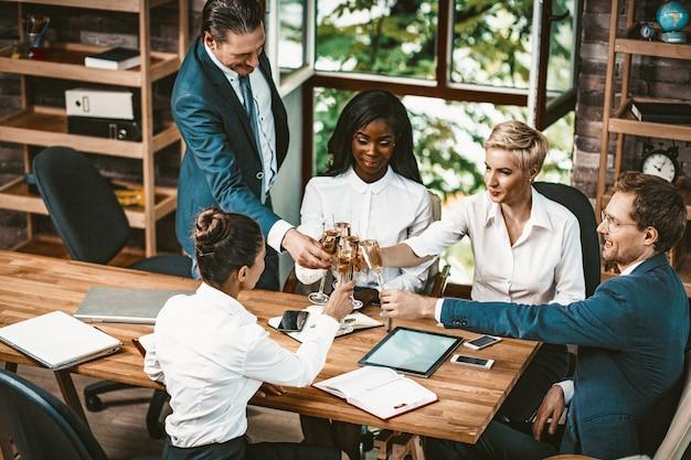多様なビジネスチームがオフィスでシャンパンを飲む