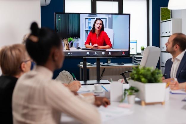 リモートエグゼクティブマネージャーとオンラインで話し合うビデオミーティングを行う多様なビジネスチーム
