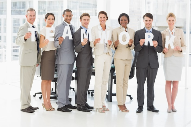 さまざまなビジネスチームは、オフィスで手紙のスペルをチームワークを保持