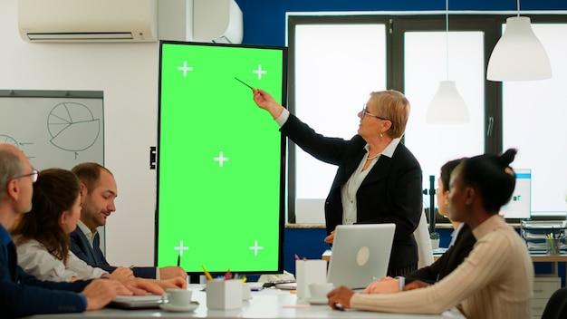 재무 통계를 분석하는 회의 테이블에 앉아 있는 다양한 비즈니스 팀은 수석 리더가 설명하는 동안 녹색 화면 디스플레이를 보고 있습니다. 크로마 키 데스크탑에서 프로젝트를 계획하는 다민족 근로자