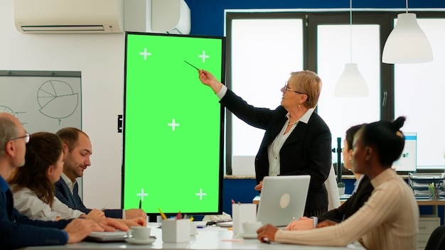 Diverse business team sitting at meeting table analysing financial statistics, looking at green screen display while senior leader explaning. multiethnic workers planning project on chroma key desktop