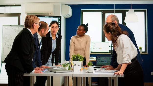 会議デスクに立ってドキュメントを探している会社のオフィスで会議中にブレーンストーミングを行う多様なビジネスマン。オフィスで話し合う成功の財務戦略を計画している同僚