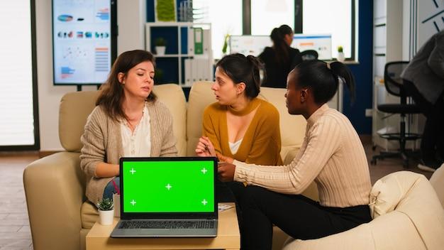 녹색 화면 모니터가 있는 노트북 뒤에 소파에 앉아 연간 재무 보고서를 분석하는 다양한 경제인. 리더는 크로마 키 디스플레이가 있는 그린스크린 pc를 사용하여 프로젝트 전략을 설명합니다.