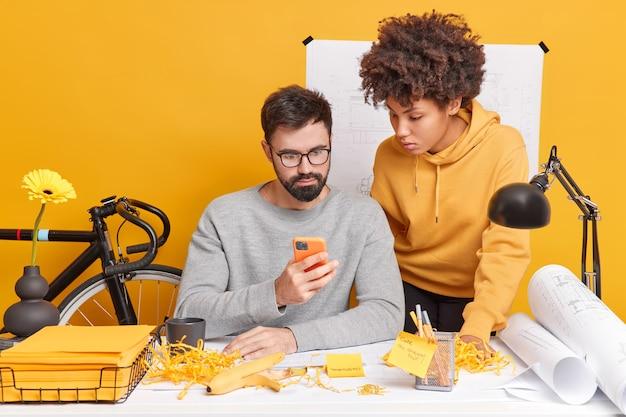 Разнообразные занятые женщина и мужчина работают вместе в офисе, сосредоточившись на смартфоне, изучите информацию с веб-сайта, внимательно посмотрите на электронную почту, разработайте новую стратегию для инженерного проекта