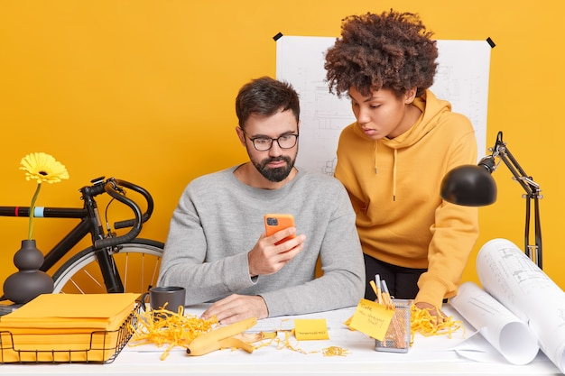 Diverse busy woman and man work together in office concentrated at smartphone learn information from website have attentive expressions check email develop new strategy for engineering project