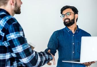 Diverse colleague men shaking hands together