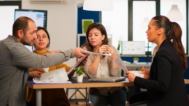ドキュメントやチャートを保持している現代のオフィスに座ってスタートアップミーティング中に会社の問題について話し合う多様な同僚のビジネスマン。マーケティングプロジェクトのために働いている多民族のビジネスチーム。