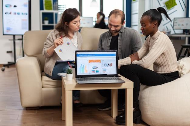 Разнообразные коллеги-сотрудники, работающие в офисе, обсуждают на рабочем месте