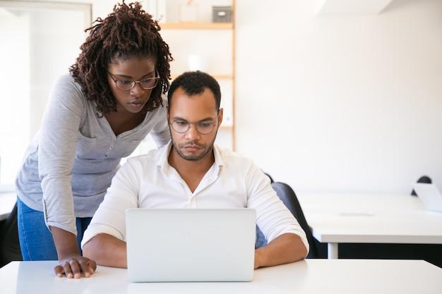 Разнообразные коллеги смотрят презентацию на компьютере