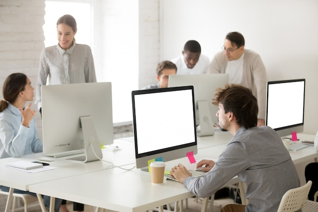 Diverse corporate employees group working together using computers in office