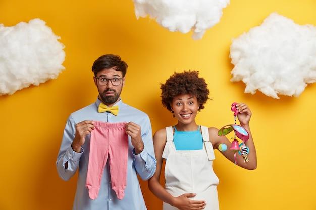 다양한 커플은 아이가 부모가 될 장난감과 옷으로 아기 포즈를 기대합니다.
