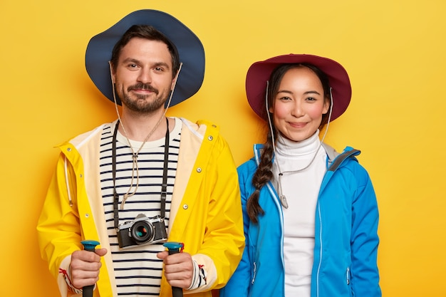 Diverse couple have hiking trip, dressed casually, pose with trekking sticks, retro camera, cover long distance on foot