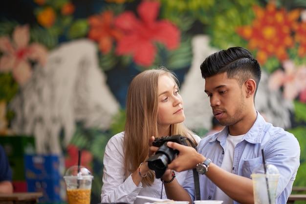 近くの町への短い旅行中にデジタルカメラで撮った写真を見ている多様なカップル