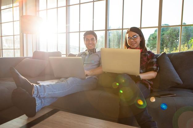Разнообразные влюбленные пары, кавказский мужчина и азиатская женщина, сидя на диване в гостиной и держа портативный компьютер портативного компьютера, работая дома вместе в оранжевом свете заката с эффектами вспышки.