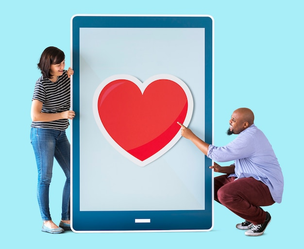 Diverse couple of people holding a tablet