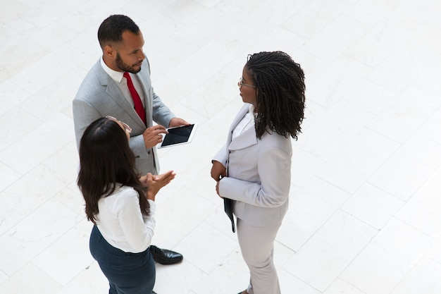 Diverse coworkers discussing project in office hallway