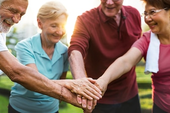 Разнообразные пожилые люди раздают вместе командную работу