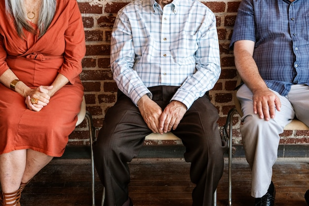 Diverse elderly people sitting in a row against a brick wall background