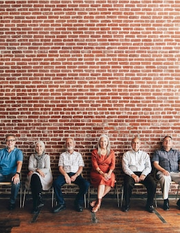 Diverse elderly people sitting in a row against a brick wall