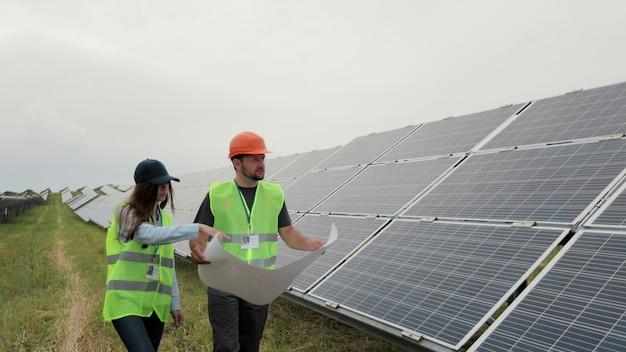 太陽エネルギー農場に立ちながら、多様なエンジニアが計画を話し、確認しています。プロジェクトを議論する作業服とヘルメットの女性と男性。グリーンエネルギーの概念。ソーラーパネルフィールド。