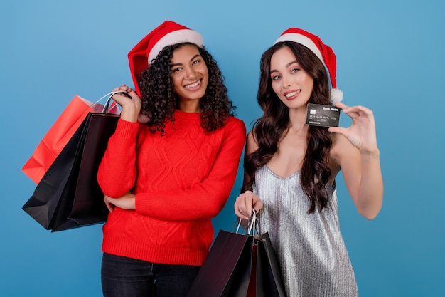 Diverse excited women with colorful shopping bags and credit card