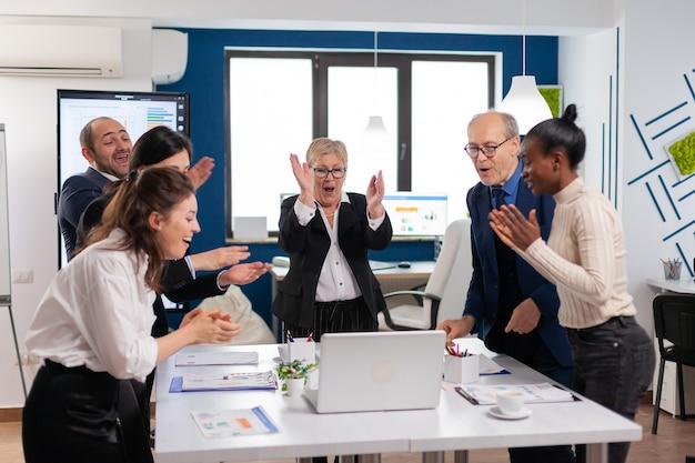 トレーニング中に会議室で拍手する多様なエグゼクティブビジネスチーム