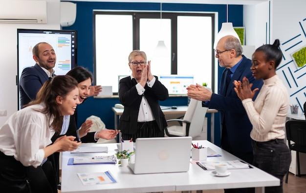 会議室で拍手する多様なエグゼクティブビジネスチーム