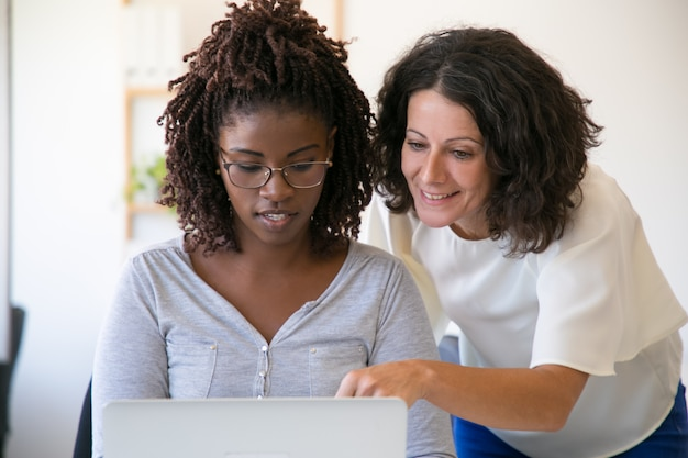 Diverse female coworkers working on computer