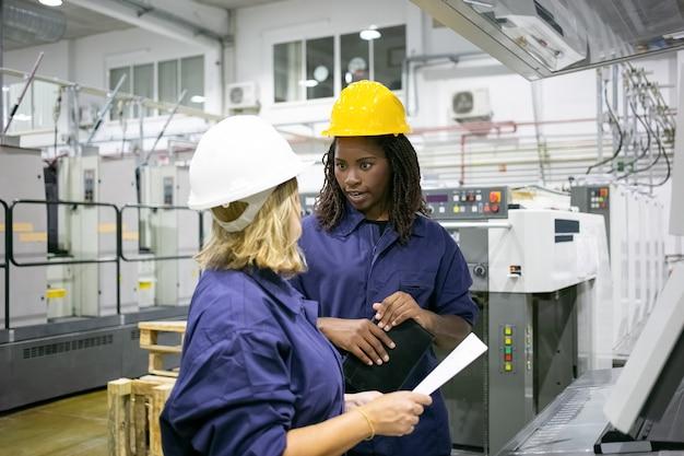 工場の床に立ってチャットしているヘルメットとオーバーオールの多様な女性工場従業員