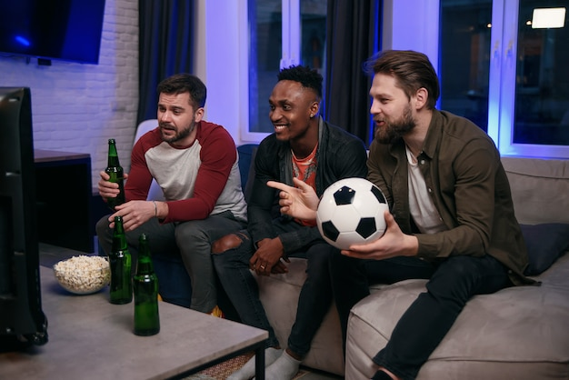 Diverse football fans cheering for favourite team and drinking beer at home, copy space