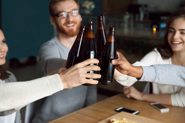 Diverse friends clinking craft beer bottles in pub, cheers concept