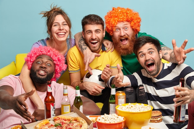 Diverse friends football supporters celebrate success of favorite team with popcorn, pizza and drinks, sit on couch, spend sunday evening in front of tv, isolated over blue wall. home cinema