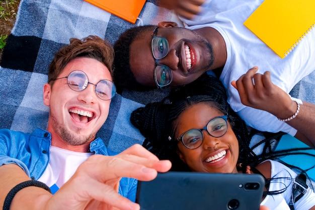 야외에서 공부하는 다양한 학생들의 친구들이 공원에서 함께 토론하며 휴식을 취합니다.