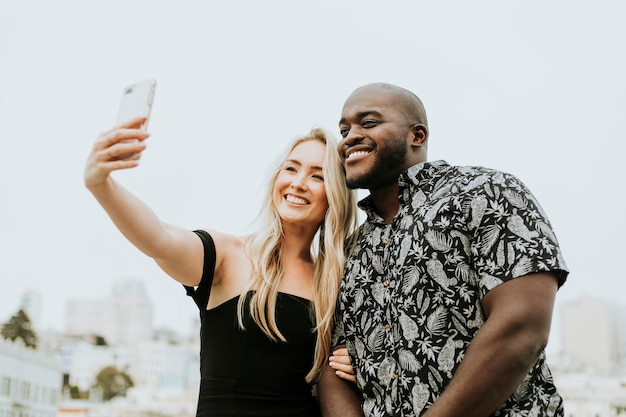 Diverse friends taking a selfie at a rooftop party