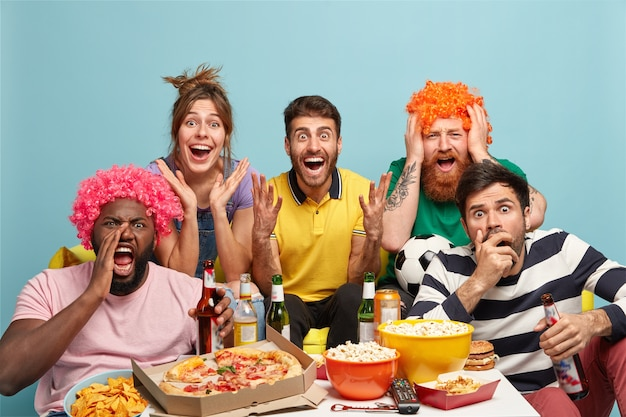 Diverse friends watch with great interest exciting movie, have surprised expressions, share snack, drink beer, wear wigs, react on interesting scene, isolated over blue wall. people, leisure