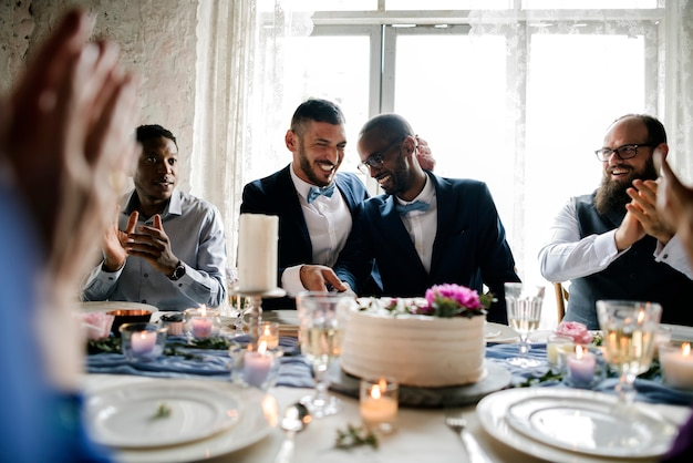 Diverse gay couple newlyweds at reception table