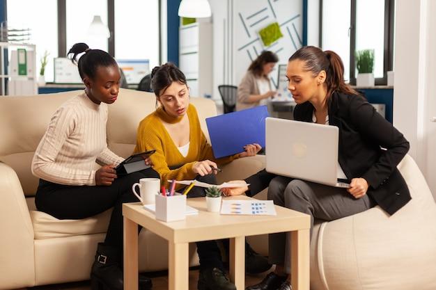 Gruppo eterogeneo di donne d'affari sedute sul divano in un moderno ufficio aziendale di startup che parlano di avvio di progetti finanziari e gestione della strategia, utilizzando computer portatile e grafica