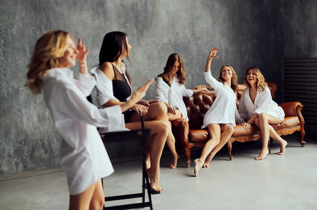 Diverse group of female friends enjoying at a party and laughing. group of beautiful women having fun and sitting on sofa.
