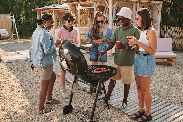Diverse group of friends frying hot dogs on grill at beach party drinking and talking