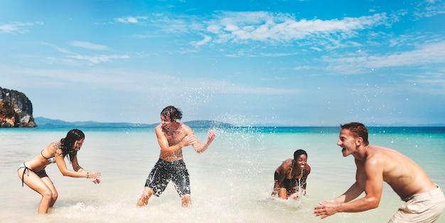 Gruppo eterogeneo di amici che giocano nell'acqua della spiaggia