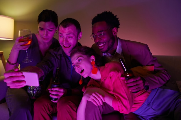 Diverse group of friends taking selfie or video chatting together during indoor party lit by purple lights