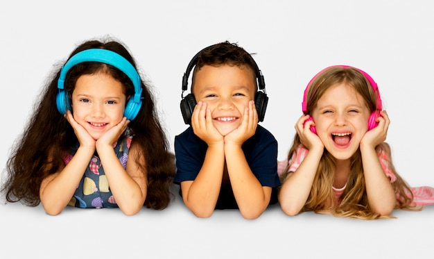 Diverse group of kids lying and listen to music in a headphones