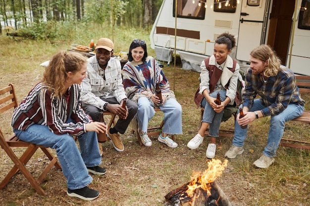 Diverse group of modern young people enjoying camping outdoors with trailer van and sitting by fire ...