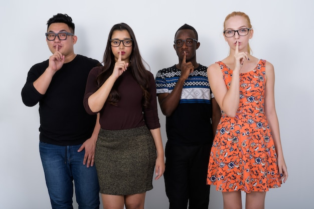 Diverse group of multi ethnic friends with fingers on their mouth